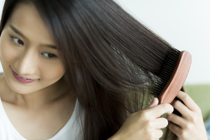 髪をとかす若い女性 FYI00497372