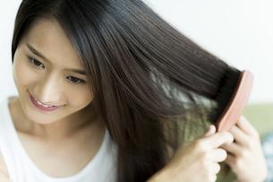 髪をとかす若い女性 FYI00497374