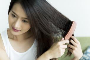 髪をとかす若い女性 FYI00497376