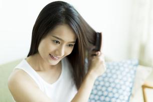 髪をとかす若い女性 FYI00497378