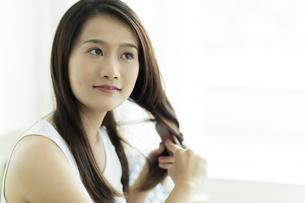 髪をとかす若い女性 FYI00497380