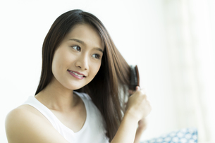 髪をとかす若い女性 FYI00497381