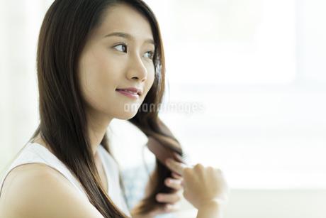 髪をとかす若い女性 FYI00497384