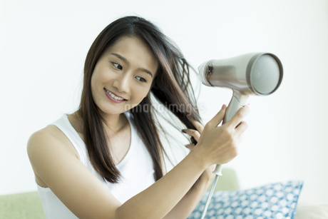 ドライヤーで髪を乾かす若い女性 FYI00497431