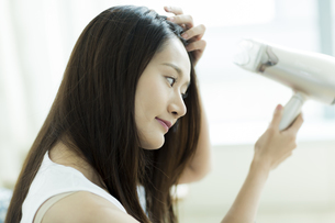 ドライヤーで髪を乾かす若い女性 FYI00497446