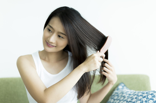 髪をとかす若い女性 FYI00497450