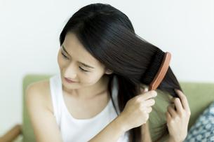髪をとかす若い女性 FYI00497455