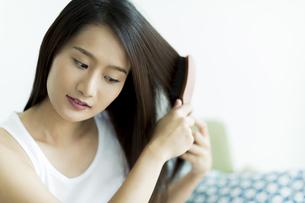 髪をとかす若い女性 FYI00497456