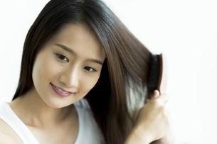 髪をとかす若い女性 FYI00497457