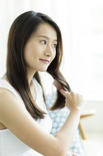 髪をとかす若い女性 FYI00497458