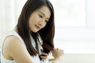 髪をとかす若い女性 FYI00497460