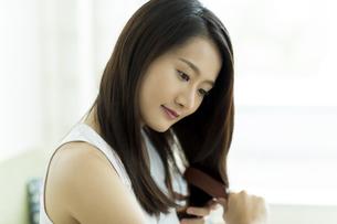 髪をとかす若い女性 FYI00497461