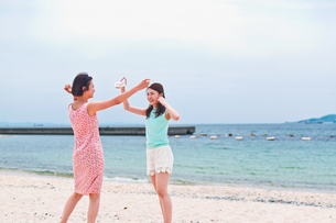 砂浜ではしゃぐ二人の女性 FYI00603480
