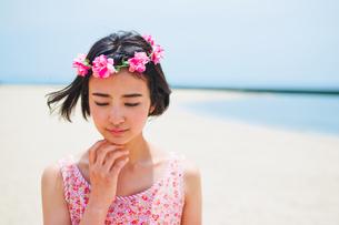 砂浜に立つ花かんむりをした女性 FYI00603485
