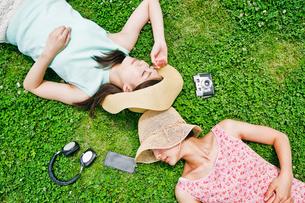 芝生に寝転ぶ二人の女性 FYI00603495