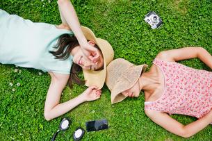 芝生に寝転ぶ二人の女性 FYI00603496