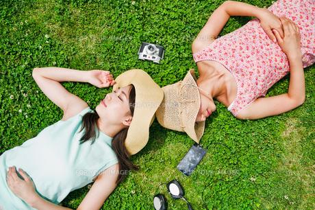 芝生に寝転ぶ二人の女性 FYI00603498