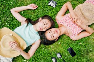 芝生に寝転ぶ二人の女性 FYI00603499