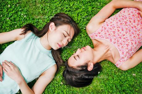 芝生に寝転ぶ二人の女性 FYI00603501
