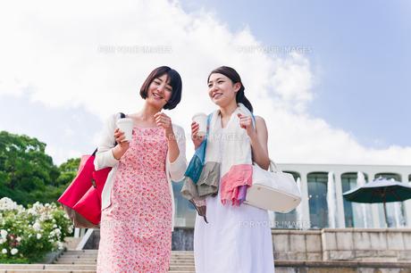 カップを片手に会話する女性 FYI00603537