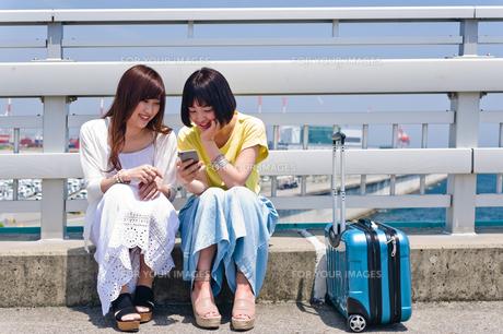 スマホを見ながら会話する女性 FYI00603628