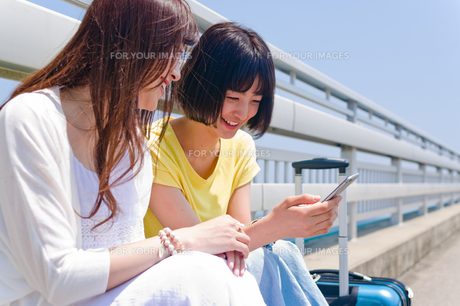 スマホを見ながら会話する女性 FYI00603629
