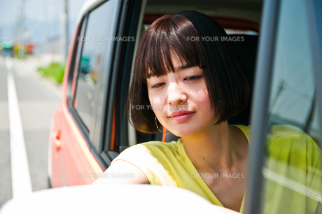 車の窓から顔を出す女性 FYI00603651