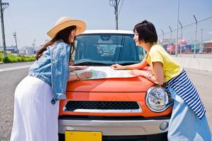 ボンネットの上で地図を広げる女性二人 FYI00603658