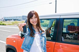 車の前で鍵を見せる女性 FYI00603661