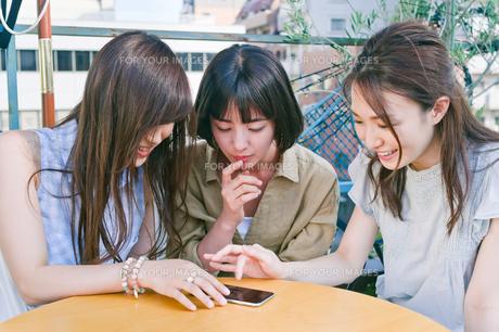 スマホを見ながら会話する女性三人 FYI00603719