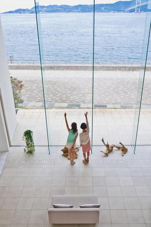海に向かって手を振る女性 FYI00603730