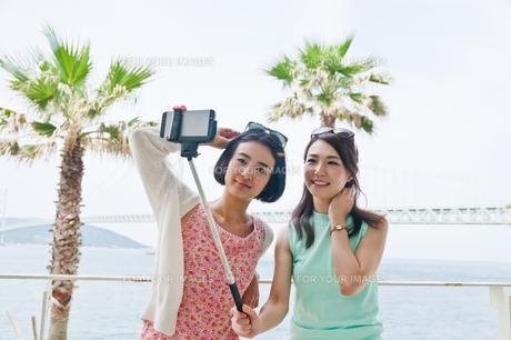 海をバックに自撮りする女性 FYI00603741