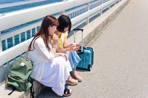 スマホを見ながら会話する女性 FYI00603749
