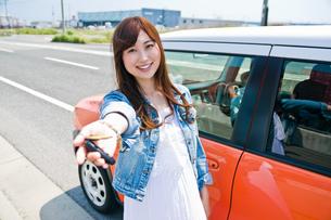 車の前で鍵を見せる女性 FYI00603755