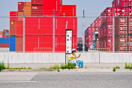 スマホを見ながらバス停でバスを待つ女性 FYI00603802