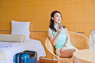 ホテルでスマホを持つ女性 FYI00603854