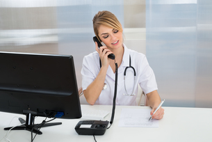 Young Female Doctor Talking On Telephone FYI00637190