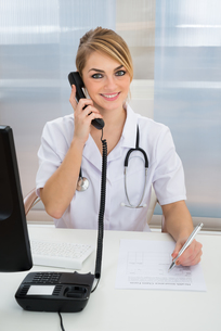 Young Female Doctor Talking On Telephone FYI00637197