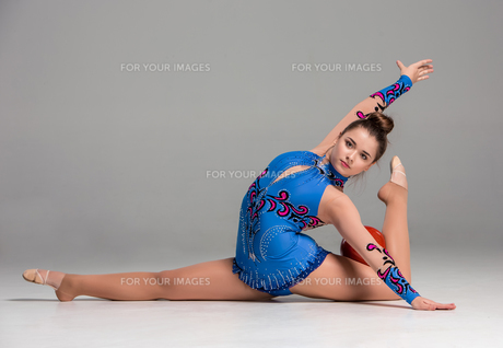 teenager doing gymnastics exercises with red gymnastic ball FYI00637381