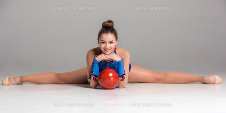 teenager doing gymnastics exercises with red gymnastic ball FYI00637386
