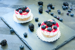 delicious strawberry cheese cake on a black plate with fresh blueberries in the background FYI00638150