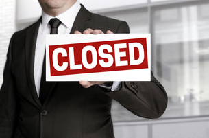 businessman holding closed counter sign FYI00643655