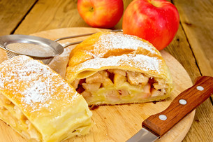 Strudel apple with strainer and knife on board FYI00645301