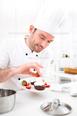 Young attractive professional chef cooking in his kitchen FYI00647326