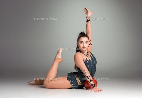 teenager doing gymnastics exercises with red gymnastic ball FYI00648744