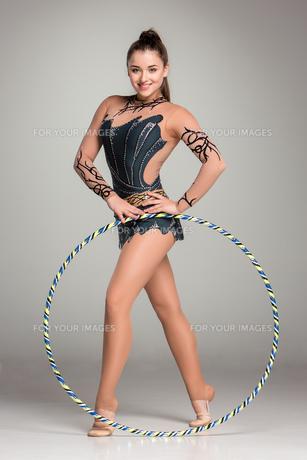 teenager doing gymnastics exercises with colorful hoop FYI00648756