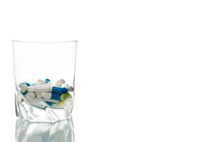 water glass filled with pillsの素材 [FYI00649731]