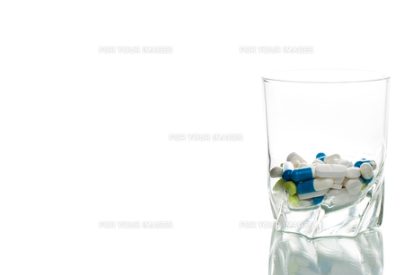 water glass filled with pills FYI00649734