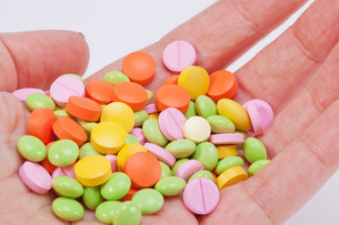 multicolored medical pills on hand FYI00650490