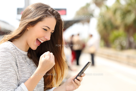 Euphoric woman watching her smart phone in a train station FYI00653967